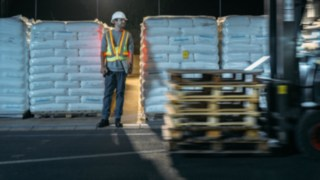 Lagerarbeiter und Stapler kreuzen sich und der Lagerarebeiter ist mit der Interaktiven Warnweste von Linde Material Handling gut sichtbar