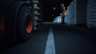 Videoausschnitt, bei dem Stapler und Lagerarbeiter treffen in dunklem Gang aufeinander treffen